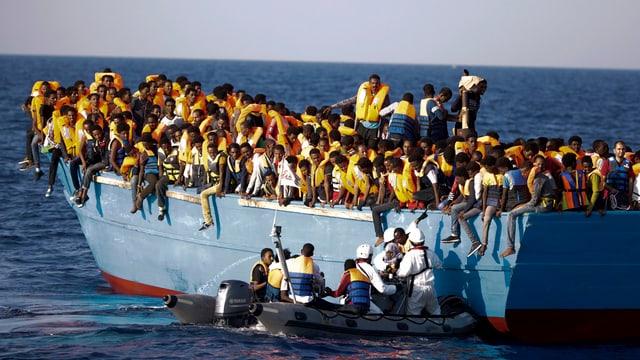 Ina bartga surchargiada cun passà 700 fugitivs sin la Mar Mediterrana. Els vegnan spindrads da gidanters talians.