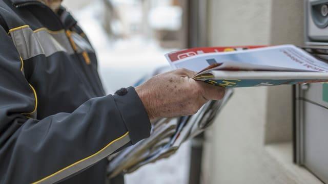 Postbote wirft Zeitschriften in einen Briefkasten.