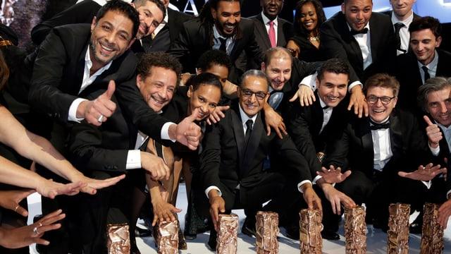 Il reschissur Abderrahmane Sissako (entamez) cun ses team poseschan cun lur premi.