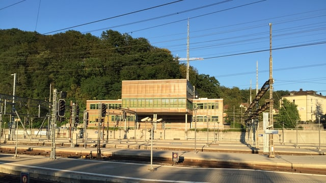 Blick von der anderen Bahnhofseite auf das Gebäude, das im Sonnenlicht statt braun fast schon golden erscheint.