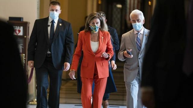 Nancy Pelosi unterwegs mit zwei Personen - alle tragen Masken.
