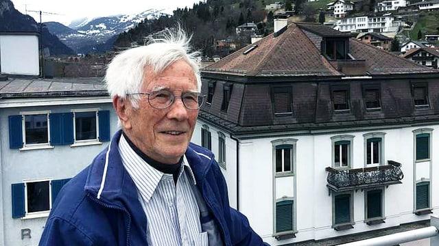 Ein älterer Mann steht auf dem Balkon.