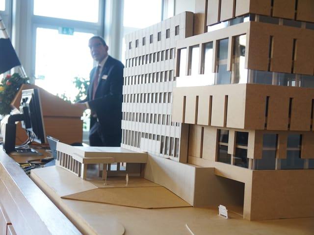 Ein Baumodell des neuen Gebäudes für die Notrufzentrale ist aufgestellt - im Hintergrund sieht man einen Mann, der an einem Rednerpult steht.