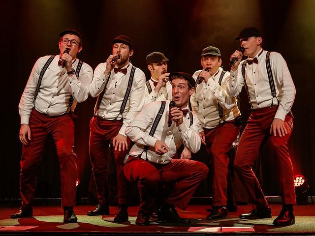 Sechs Männer in denselben Kleidern singen auf der Bühne.