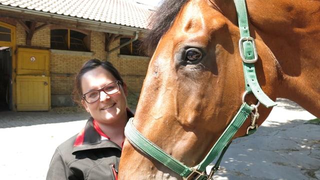 Frau mit Pferd, sie hält es am Zaum.