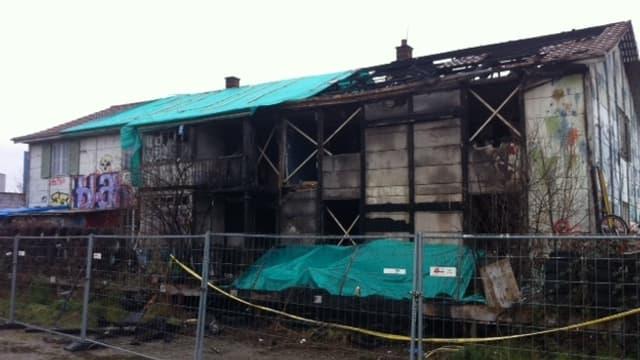 Ein verkohltes Haus, das zerstörte Dach ist mit Blachen abgedeckt.