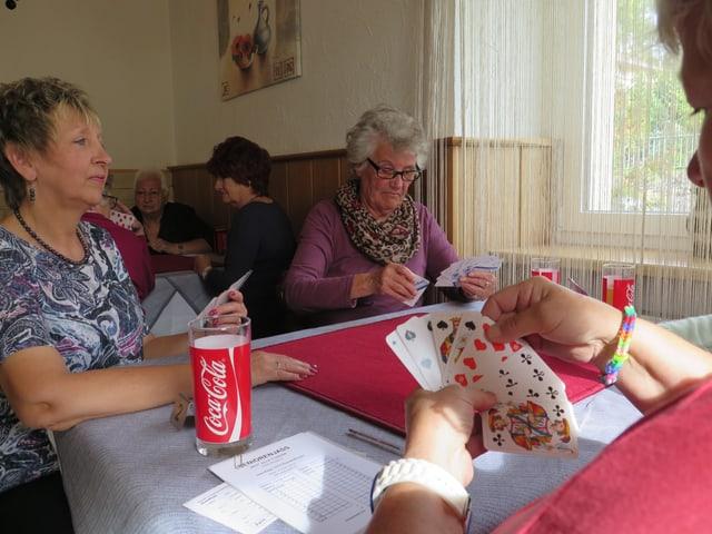 Frauen an einem Tisch in einem Restaurant, Getränke, Jasskarten in den Händen.