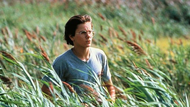River Phoenix steht für den Film «Running on Empty» mit einer Brille auf der Nase in einem weiten Feld.