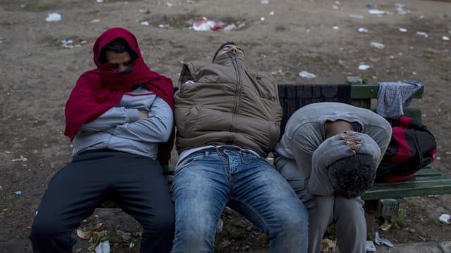 Drei Männer übernachten im Sitzen auf einer Parkbank, die Pullis um den Kopf gewickelt.