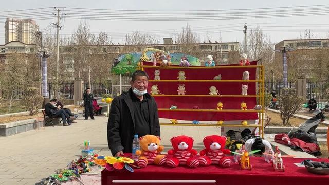 Mann posiert an Verkaufsstand mit Teddybären
