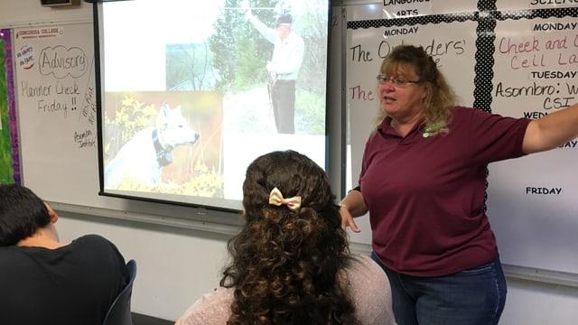 Lehrerin spricht zu Schülern.
