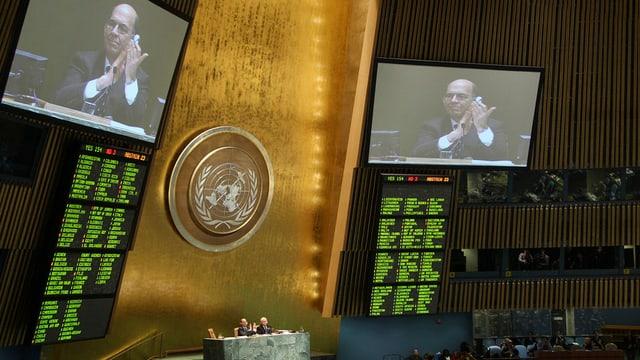 UNO-Delegierte freuen sich, wie auf der Video-Leinwand der Vollversammlung zu sehen ist.