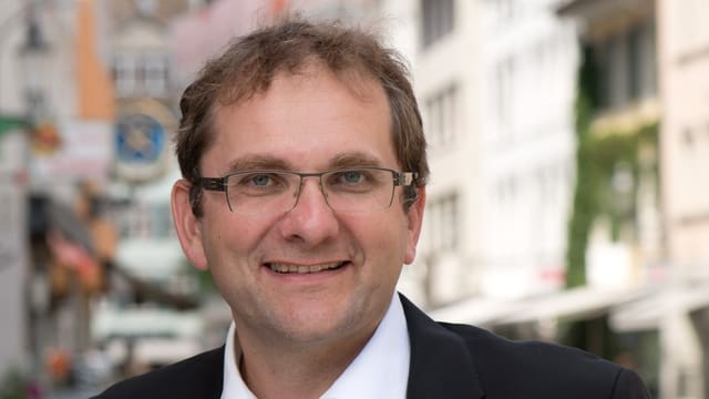 Mann mit Brille und kurzen braunen Haaren