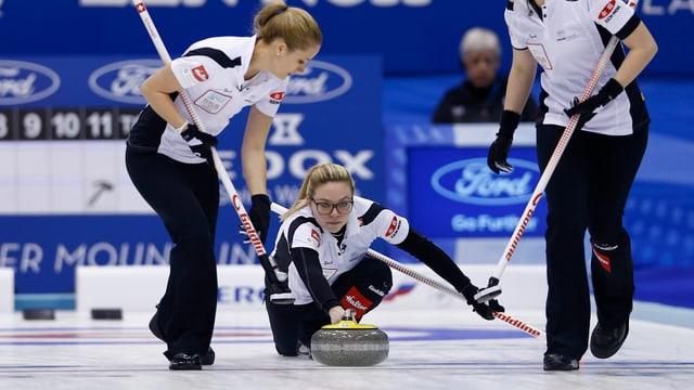 Eine Frau schiebt ein Curlingstein über das Eis.