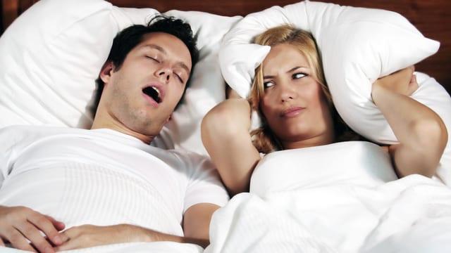 Paar liegt im Bett. Er schnarcht, sie hält sichmit dem Kissen die Ohren zu und schaut missbilligend drein.