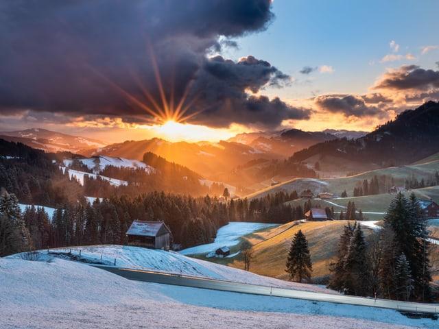 Sonnenuntergang über einer leicht verschneiten Hügellandschaft bei wechselnder Bewölkung.