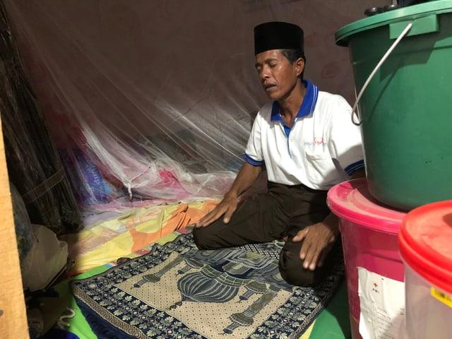Indonesischer Mann kniet auf dem Boden und betet.