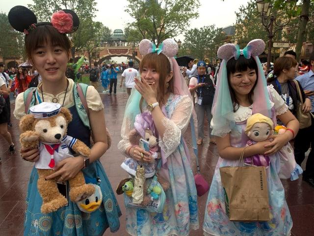 Chinesische Besucherinnen mit Mickey-Mouse-Hüten im Disneyland Shanghai