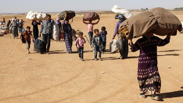 Syrische Familien tragen grosse Pakete auf dem Kopf und ziehen über eine Landstrasse.