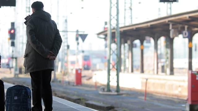 Ein Mann mit Koffer an einem Bahnsteig.