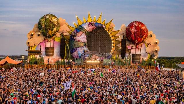 Viele Festivalbesucher vor einer grossen Bühne. Bühne ist eine riesige Sonne mit links und rechts je ein Luftballon.