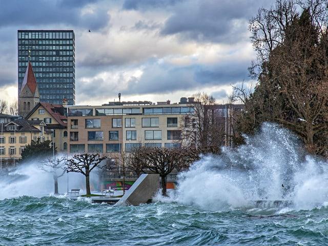 Wellen spritzen Wasser meterhoch.