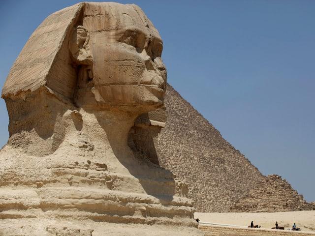 Bild einer grossen, steinernen Sphinx, im Hintergrund eine Pyramide.