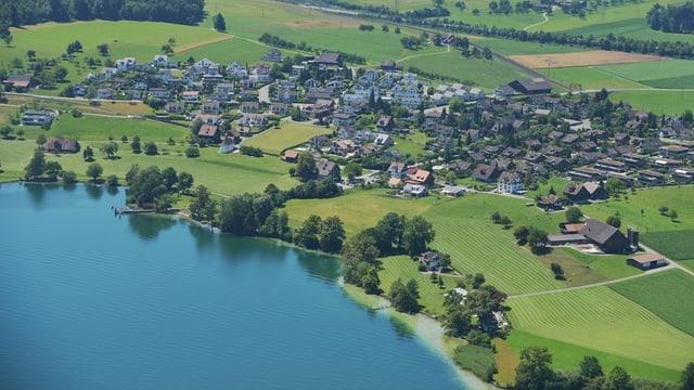 See mit einem grünen Ufer aus Landwirtschaftsland - ein Dorf im Hintergrund.