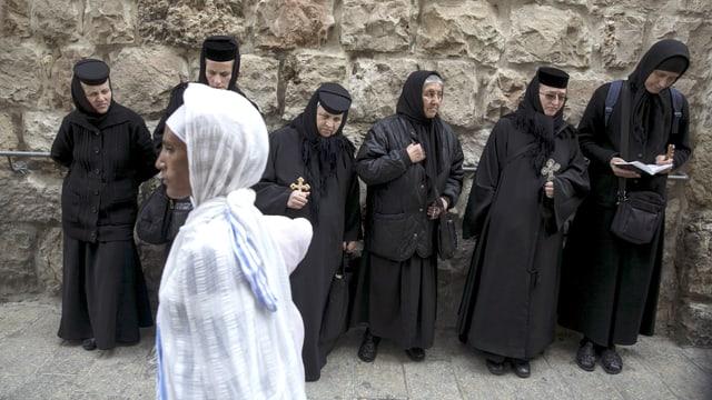 Eine Frau im weissen Gewand geht vorbei an orthodoxen Nonnen.