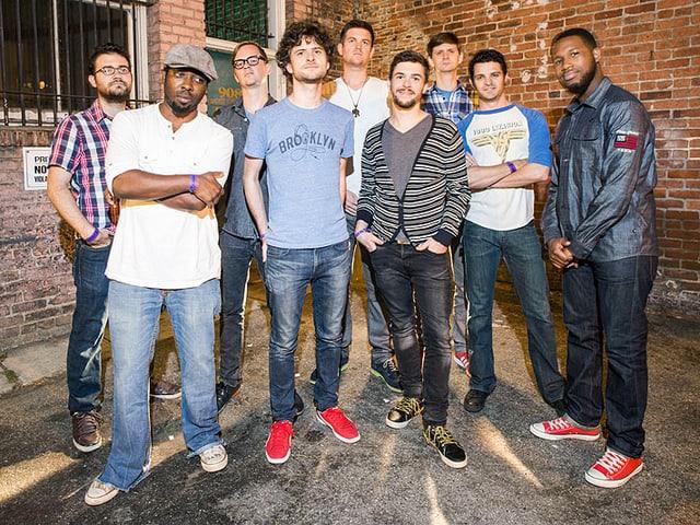 Ein Bandfoto mit mehreren Musikern. Sie stehen vor einer Wand.