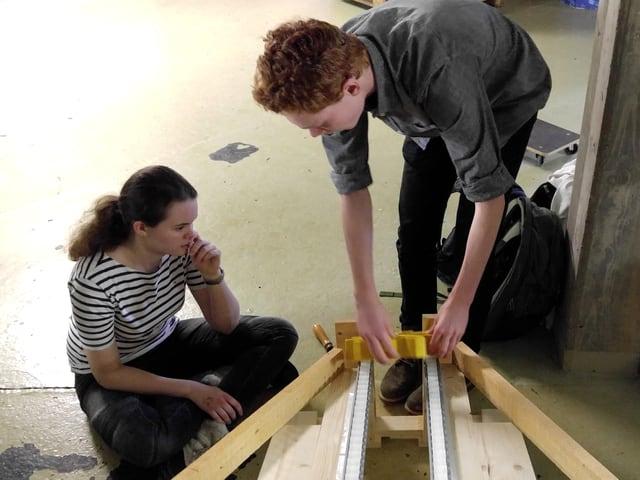 Nina und Luca diskutieren eine von zwei Möglichkeiten, die Zahnräder in den Roboter «einzufüllen».