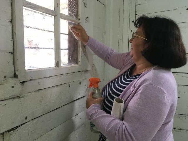 Eine Frau putzt ihre Fenster.