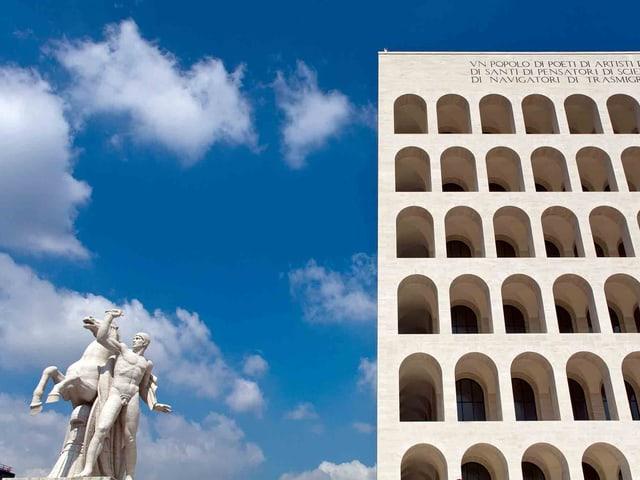 Ein mit Gebäude mit vielen Bogenfenstern, daneben eine Statue eines Mannes mit Pferd.