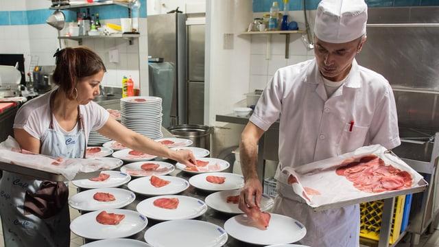 Koch und eine Gehilfin richten Teller in einer Restaurantküche an