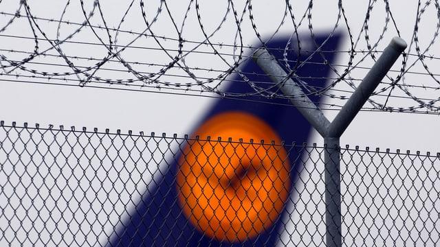 Ein Lufthansa-Flugzeug hinter einem Zaun mit Stacheldraht.