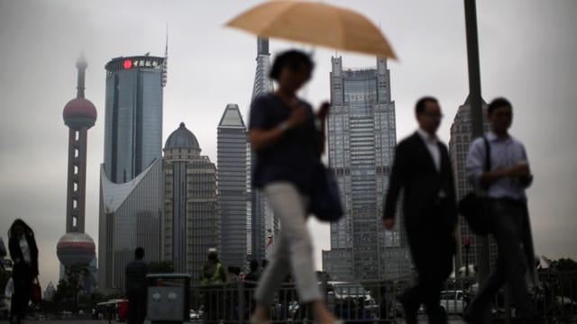 Passanten – im Hintergrund das Pudong Finanzviertel im Shanghai.