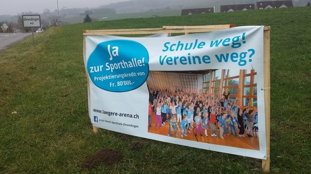 Plakat der Sporthallen-Befürworter vor dem Ortsschild von Ehrendingen.