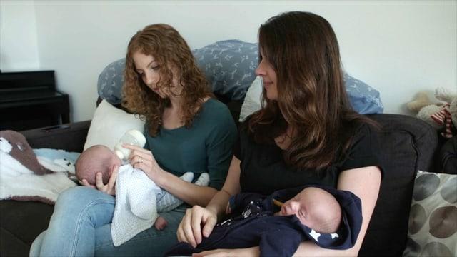 zwei Frauen geben zwei Babies die Flasche
