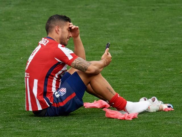 Luis Suarez sitz mit dem Handy auf dem Rasen.