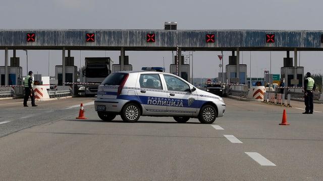 Polizeiauto versperrt Strasse vor Grenzübergang.
