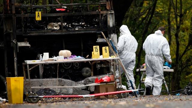 Zwei Forensiker in Schutzkleidung vor dem ausgebrannten Bus