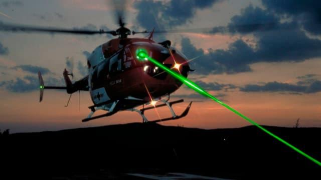Ein Rega-Helikopter bei Dämmerung, auf den ein grüner Laserstrahl gerichtet ist (Photomontage).