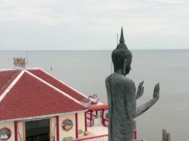 Statue hält Hände in die Höhe. Im Hintergrund sieht man ein Gebäude der Tempelanlage.