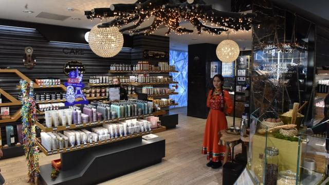 Aufnahme des edlen Kosmetikladens. Eine Verkäuferin steht in einer orangen Tracht in einer Ecke.