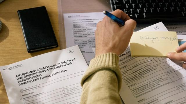 Eine Hand über Formularen zur Beantragung von Sozialhilfe