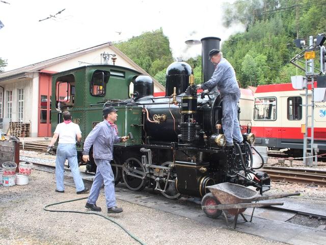 Mitglieder des Vereins Dampfzug Waldenburgerbahn werkeln an der Lok.