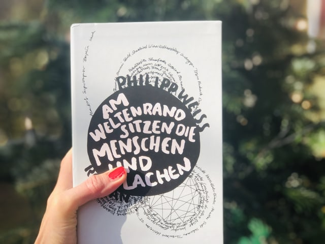 Der Roman von Philipp Weiss: «Am Weltenrand sitzen die Menschen und lachen» vor einem Tannebaum hingehalten