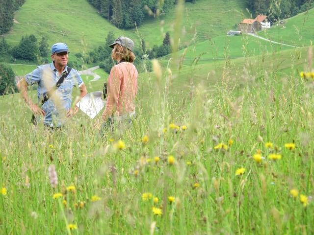 Zwei Menschen stehen in einer Blumenwiese.