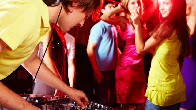 DJ mischt Musik, im Hintergrund tanzende Menschen