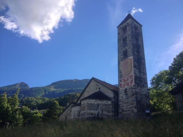 Foto der Kirche mit Zeichnungen der Urner Wappen am Kirchturm